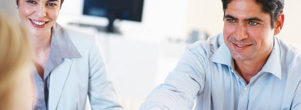 Smart business man sitting at table and shaking hands with colleague during meeting